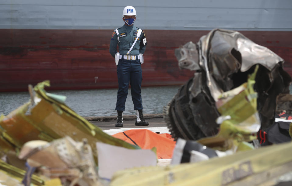 An Indonesian soldier stand guard near debris found in the waters around the location where a Sriwijaya Air passenger jet crashed at the search and rescue command center at Tanjung Priok Port in Jakarta, Indonesia, Friday, Jan 15, 2021. More searchers and rescuers joined the search Friday for wreckage and victims from an Indonesian plane that crashed last weekend in the Java Sea. (AP Photo/Achmad Ibrahim)