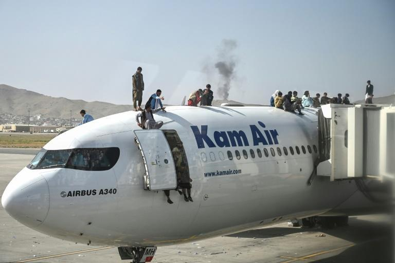 Afghan people climb atop a plane at the Kabul airport on August 16, 2021, after a stunningly swift end to Afghanistan's 20-year war, as thousands of people tried to flee the Taliban (AFP/Wakil Kohsar)