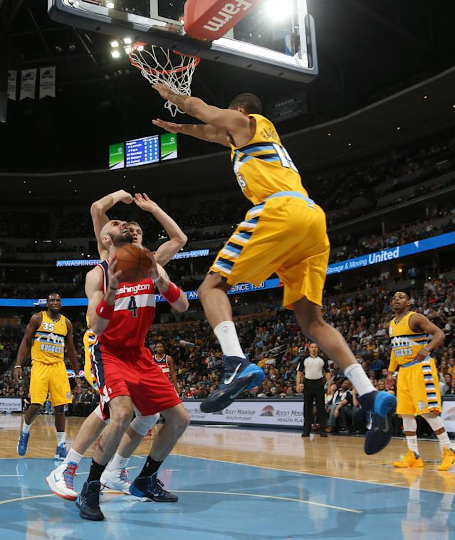 Washington Wizards center Marcin Gortat, front left, of Poland, goes up for shot as Denver Nuggets forward Anthony Randolph, right, and center Timofey Mozgov, back left, of Russia, cover in the first quarter of an NBA basketball game in Denver on Sunday, March 23, 2014. (AP Photo/David Zalubowski)