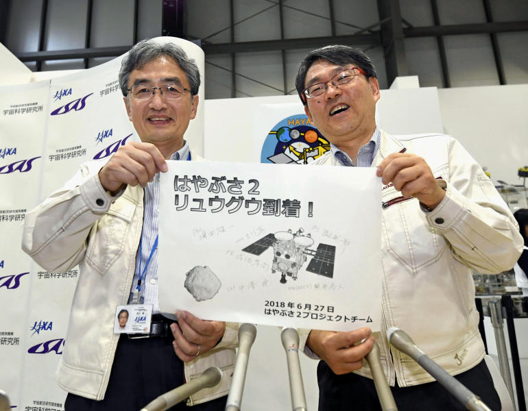 """Professor Takashi Kubota, right, and Associate Professor Makoto Yoshikawa, both of JAXA, the Japanese space agency, pose for photo, after asteroid explorer Hayabusa2 has arrived at the asteroid of Ryugu, in Sagamihara, near Tokyo, Wednesday, June 27, 2018. The Japanese space explorer arrived at an asteroid Wednesday after a three and half a year journey and now begins its real work of trying to blow a crater to collect samples to eventually bring back to Earth. The words in center, read """"Hayabusa2 has arrived Ryugu"""". (Daisuke Suzuki/Kyodo News via AP)"""