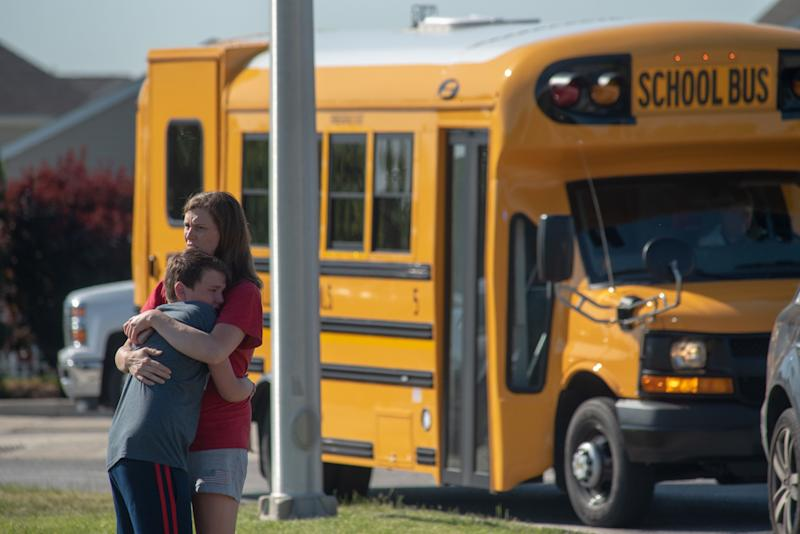 A student and adult embrace outside Noblesville West Middle School after a shooting at the Indiana school on Friday.