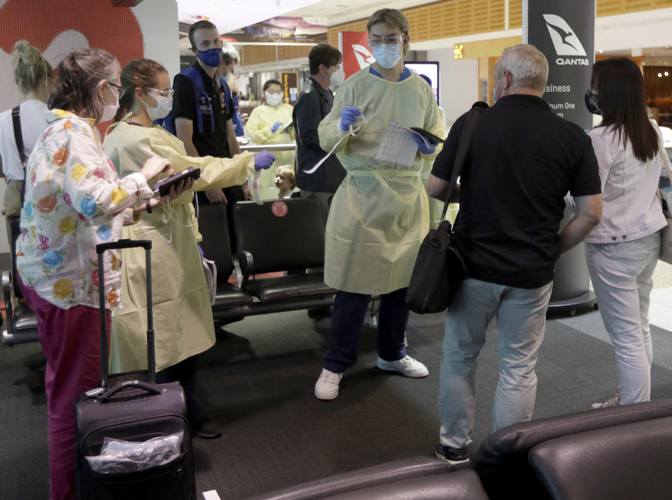 Passengers arriving from Melbourne are screened by health workers at the airport in Sydney.