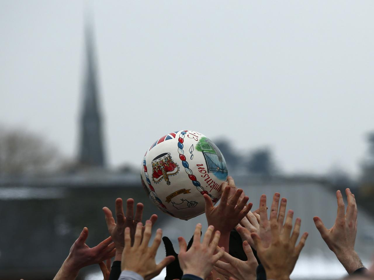 <p>The ball is momentarily suspended in the air as a crowd of hands reach up to grab it (Reuters)</p>