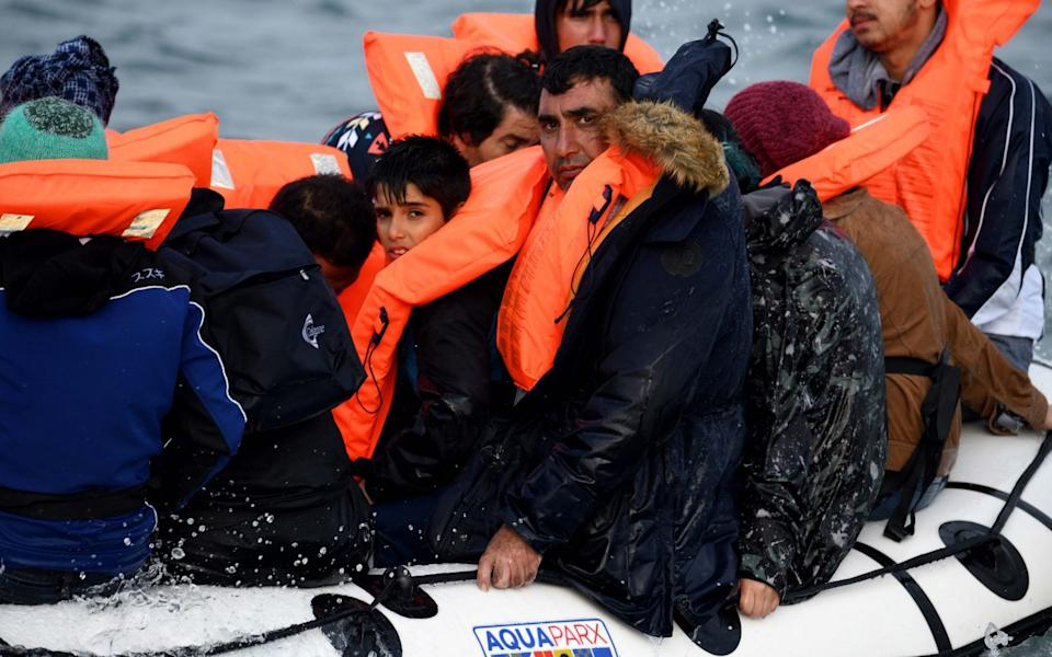Migrants heading for the UK are seen bailing water from their dinghy - Steve Finn