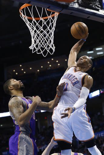 Oklahoma City Thunder guard Russell Westbrook (0) goes up for a dunk in front of Phoenix Suns forward Markeiff Morris (11) in the third quarter of an NBA basketball game in Oklahoma City, Friday, Feb. 8, 2013. Oklahoma City won 127-96. (AP Photo/Sue Ogrocki)