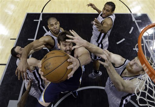 Memphis Grizzlies' Marc Gasol, center, is defended, from left, by San Antonio Spurs' Manu Ginobili, Tim Duncan, Kawhi Leonard, and Matt Bonner during the first half in Game 1 of a Western Conference Finals NBA basketball playoff series, Sunday, May 19, 2013, in San Antonio. (AP Photo/Eric Gay)