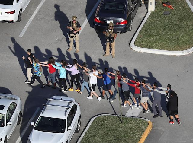 <p>People are brought out of the Marjory Stoneman Douglas High School after a shooting at the school that reportedly killed and injured multiple people on Feb. 14, 2018 in Parkland, Fla. (Photo: Joe Raedle/Getty Images) </p>