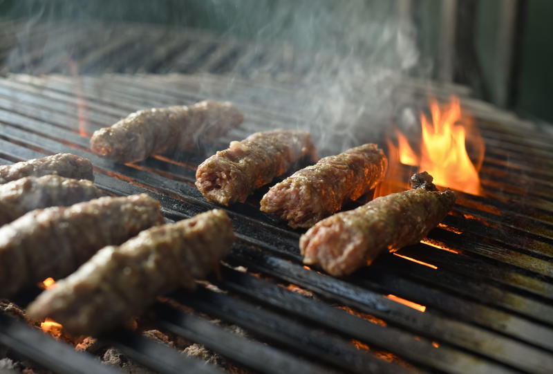 """Mici"", the Romanian version of a Turkish dish, spicy grilled sausages, popular across the Balkans, are grilled in a restaurant in Bucharest, Romania, Sunday, Feb. 16, 2014. Officials in Brussels have agreed that spicy ""mici"", grilled meat bullet shaped delicacies which rely on a pinch of bicarbonate of soda for their distinctive succulent flavor and puffy texture will be permitted under European Union rules, the Romanian Meat Association says.(AP Photo/Octav Ganea/Mediafax) ROMANIA OUT"