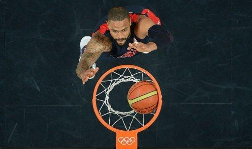 PICTURE TAKEN WITH A ROBOTIC CAMERA - US centre Tyson Chandler scores during the Men's preliminary round group A basketball match of the London 2012 Olympic Games Tunisia vs USA on July 31, 2012 at the basketball arena in London