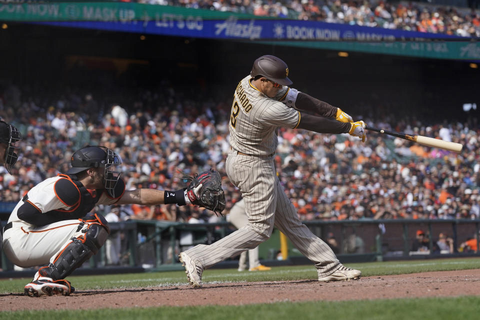 San Diego Padres' Manny Machado hits a two-run single in front of San Francisco Giants catcher Curt Casali during the eighth inning of a baseball game in San Francisco, Thursday, Sept. 16, 2021. (AP Photo/Jeff Chiu)