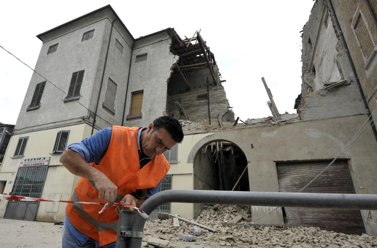 A volunteer ropes off the area surrounding a collapsed building in Finale Emilia, northern Italy after a quake hit northern Italy early Sunday, May 20, 2012. One of the strongest earthquakes to shake northern Italy rattled the region around Bologna early Sunday, a magnitude-6.0 temblor that killed at least four people, toppled buildings and sent residents running into the streets, emergency services and news reports said. (AP Photo/Marco Vasini)