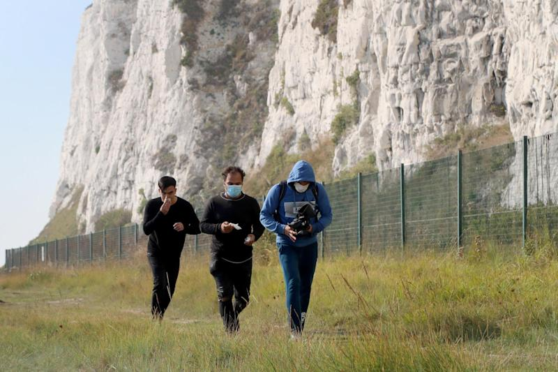 A group of people thought to be migrants on the coastline by the White Cliffs of Dover, Kent, after crossing the English Channel by small boat (PA)