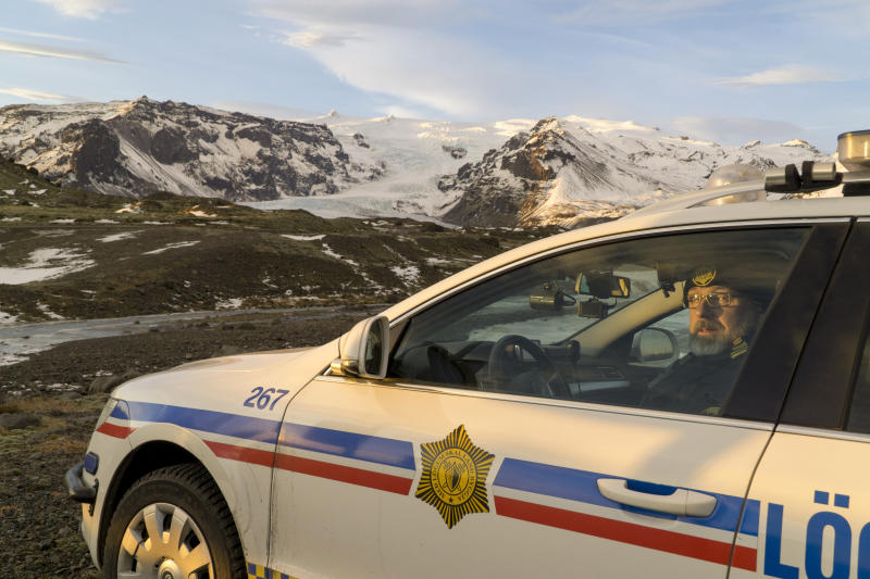 Police inspector Adolf Arnason poses for a photo at the foot of Oraefajokull volcano in Iceland, Thursday, Nov. 30, 2017. The Oraefajokull volcano, dormant since its last eruption in 1727-1728, has seen a recent increase in seismic activity and geothermal water leakage that has worried scientists. With the snow hole on Iceland's highest peak deepening 18 inches (45 centimeters) each day, authorities have raised the volcano's alert safety code to yellow. (AP Photo/David Keyton)