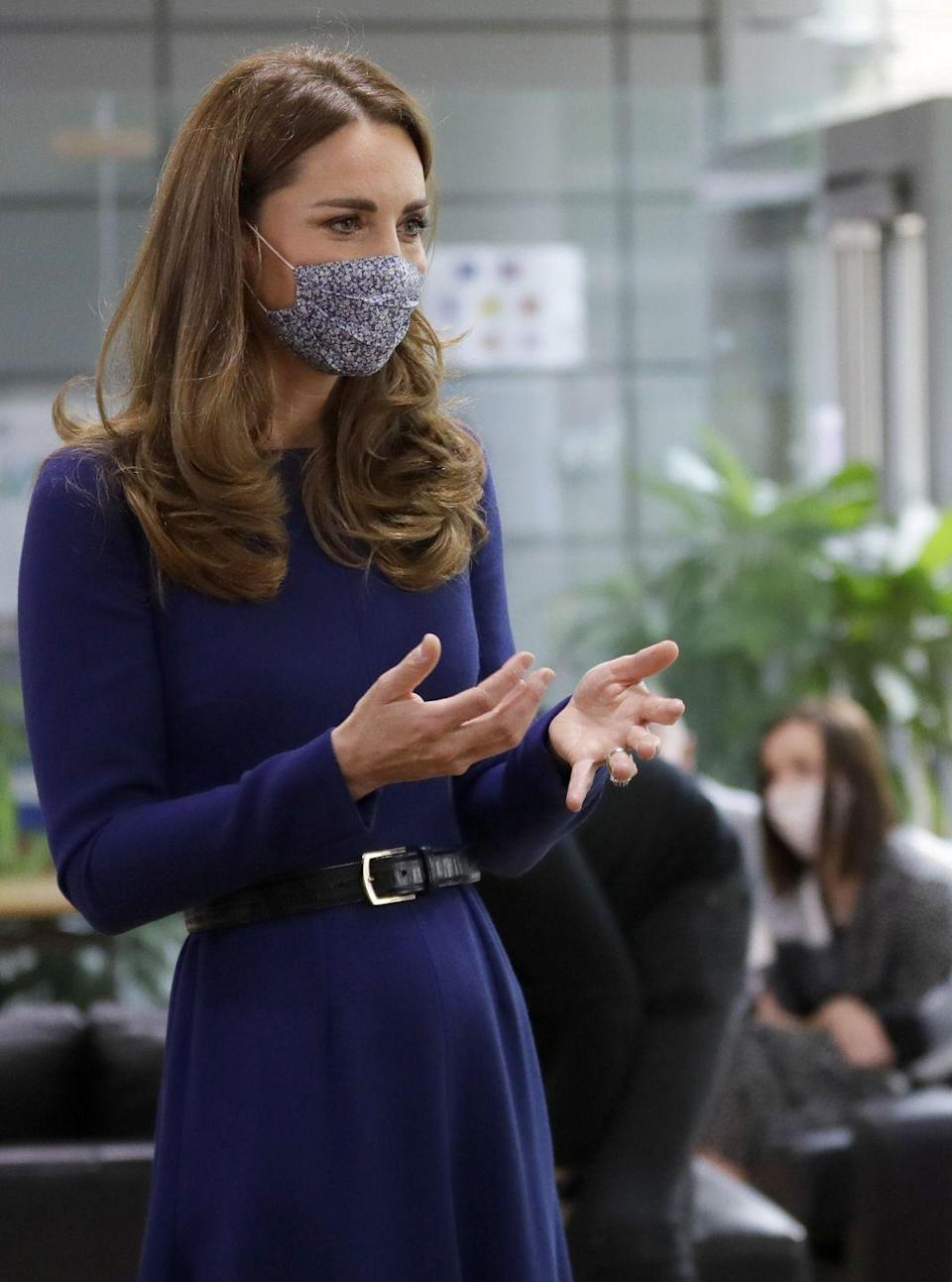"<p>The Duchess of Cambridge visited the Institute of Reproductive and Development Biology at London's Imperial College. Though she wore a white lab coat for most of the day, underneath, Kate sported an indigo, long-sleeved Emilia Wickstead dress, with a black belt and blue floral mask. </p><p><a class=""link rapid-noclick-resp"" href=""https://go.redirectingat.com?id=74968X1596630&url=https%3A%2F%2Fwww.net-a-porter.com%2Fen-us%2Fshop%2Fproduct%2Femilia-wickstead%2Fjorgie-ruched-cloque-midi-dress%2F1262324&sref=https%3A%2F%2Fwww.townandcountrymag.com%2Fstyle%2Ffashion-trends%2Fnews%2Fg1633%2Fkate-middleton-fashion%2F"" rel=""nofollow noopener"" target=""_blank"" data-ylk=""slk:Shop a Similar Style"">Shop a Similar Style</a></p>"