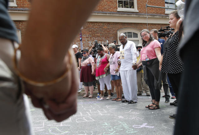 <p>A couple hold hands as the participate in prayers at the intersection where Heather Heyer was killed last year as they mark the anniversary of the Unite the Right rally in Charlottesville, Va., Sunday, Aug. 12, 2018. On that day, white supremacists and counterprotesters clashed in the city streets before a car driven into a crowd struck and killed Heyer. (Photo: Steve Helber/AP) </p>