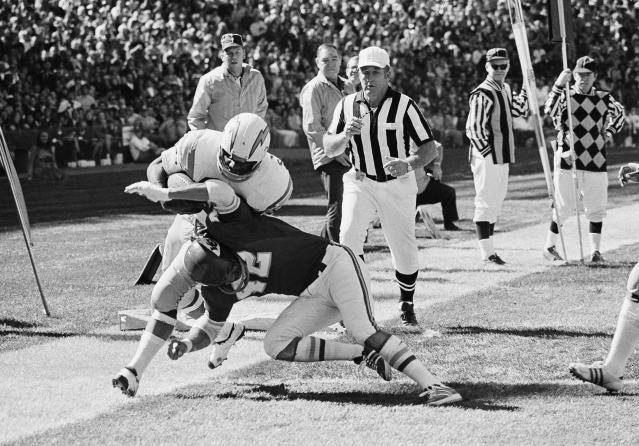 Chiefs safety Johnny Robinson, pictured in a 1971 game making a tackle against the Chargers' Mike Garrett, finished his pro career with 57 interceptions. (AP)