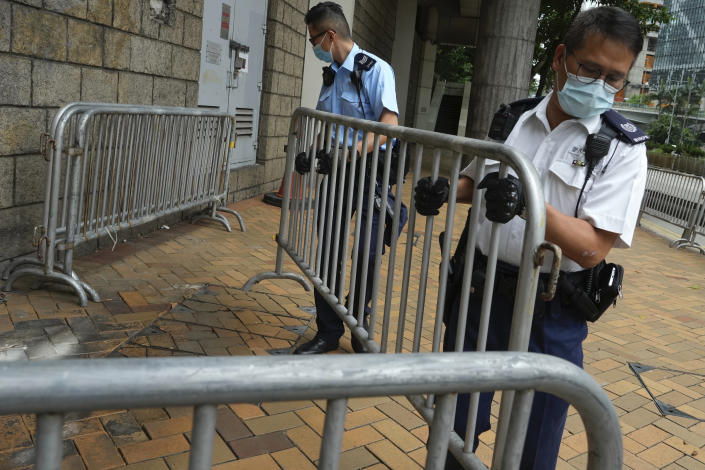 """Police officers set up barriers as they wait for Tong Ying-kit's arrival at the Hong Kong High Court in Hong Kong Friday, July 30, 2021. Tong Ying-kit was convicted Tuesday of inciting secession and terrorism for driving his motorcycle into a group of police officers during a July 1, 2020, pro-democracy rally while carrying a flag bearing the banned slogan, """"Liberate Hong Kong, revolution of our times."""" Tong, 24, will be sentenced Friday, the court announced. (AP Photo/Vincent Yu)"""
