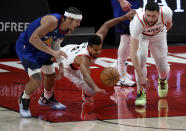 Denver Nuggets forward Aaron Gordon, left, and Portland Trail Blazers guard CJ McCollum, center, and center Jusuf Nurkic after a loose ball during the first half of an NBA basketball game in Portland, Ore., Wednesday, April 21, 2021. (AP Photo/Steve Dykes)