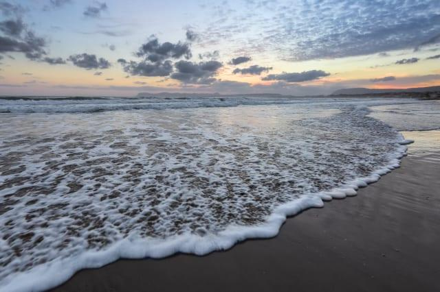 High waves with foam spread on the sand on the coast. The light of unbelievable sunset is reflecting on the sea. Pre dawn time. Beautiful enlighten sky with clouds. Mountains. Romantic relax place.