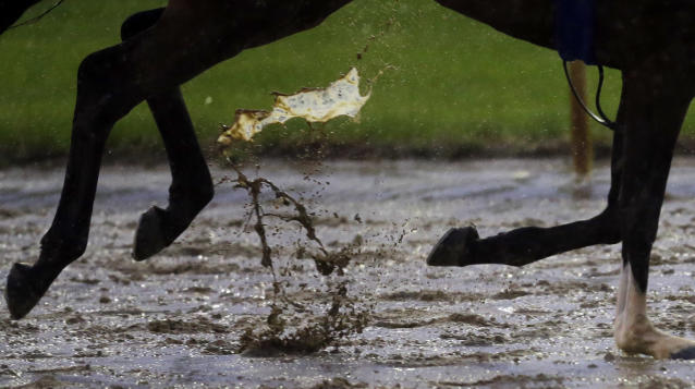 A horse runs on the wet track at Churchill Downs Monday, April 28, 2014, in Louisville, Ky. (AP Photo/Morry Gash)
