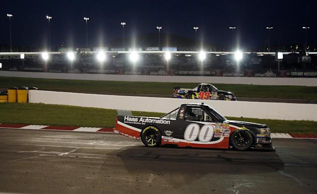 Cole Custer (00) exits Turn 4 as Bryan Silas (99) heads in for the pits during the NASCAR Truck Series auto race at Gateway Motorsports Park pn Saturday, June 14, 2014, in Madison, Ill. (AP Photo/Jeff Roberson)