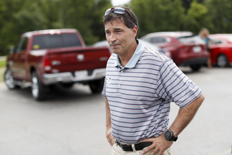 Republican Troy Balderson, a candidate for Ohio's 12th District, stands in the parking lot of a voting precinct at Genoa Baptist Church, Tuesday, Aug. 7, 2018, in Westerville, Ohio. Balderson, is fighting off a strong challenge from Democrat Danny O'Connor, 31-year-old county official, in a congressional district held by the Republican Party for more than three decades. (AP Photo/John Minchillo)