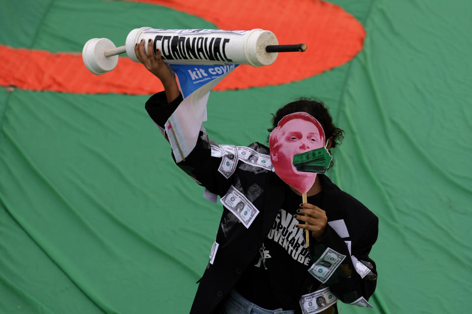 A demonstrator wears a mask depicting Brazil's President Jair Bolsonaro with a mouthful of U.S. dollars, while holding a syringe representing the COVID-19 vaccine, during a protest against Bolsonaro, calling for his impeachment over his government's handling of the pandemic and accusations of corruption in the purchases of COVID-19 vaccines, in in Brasilia, Brazil, Saturday, Oct. 2, 2021. (AP Photo/Eraldo Peres)