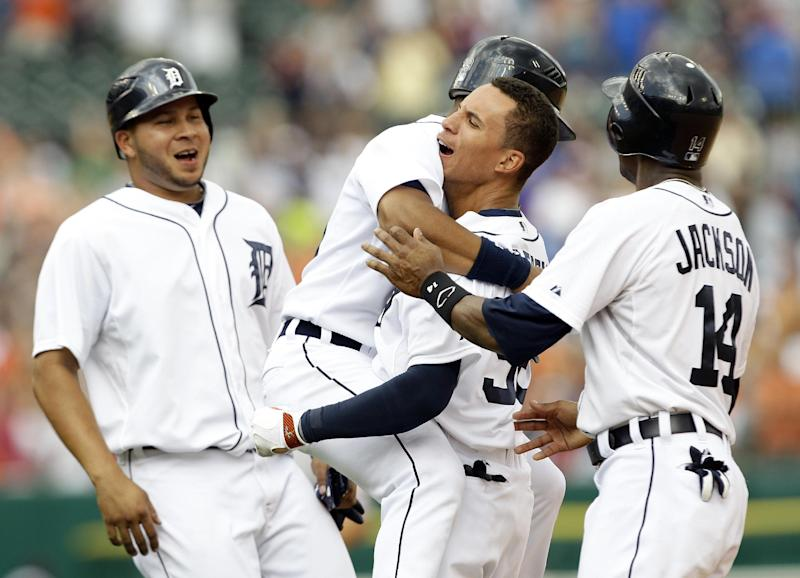 Detroit Tigers center fielder Quintin Berry, third from left, celebrates after hitting an RBI-single with, from left, Jhonny Peralta, Ramon Santiago, and Austin Jackson (14) in the 10th inning of a baseball game against the St. Louis Cardinals in Detroit, Thursday, June 21, 2012. Detroit won 2-1.  (AP Photo/Paul Sancya)