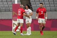 Madison Hughes, center, of the United States greets Britain's Tom Bowen, left, and Alex Davis after the U.S. team lost to Britain during their men's rugby sevens quarterfinal match at the 2020 Summer Olympics, Tuesday, July 27, 2021, in Tokyo. (AP Photo/Shuji Kajiyama)