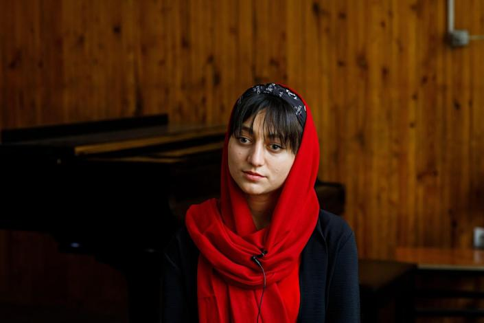 A young female musician wearing red and black.