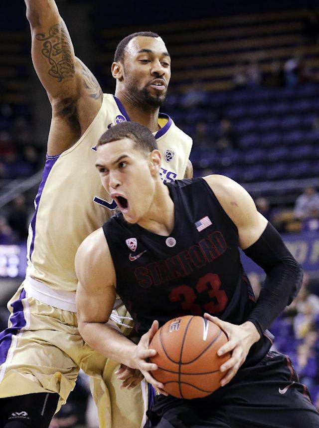 Stanford's Dwight Powell (33) tries to drive past Washington's Desmond Simmons in the first half of an NCAA college basketball game Wednesday, Feb. 12, 2014, in Seattle. (AP Photo/Elaine Thompson)