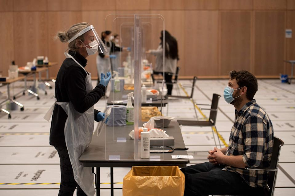 A member of staff instructs a student on how to self-administer a swab for a lateral flow Covid-19 test at the University of Hull (AFP via Getty Images)