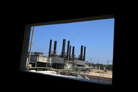 Gaza power plant is seen through a building window, in the central Gaza Strip