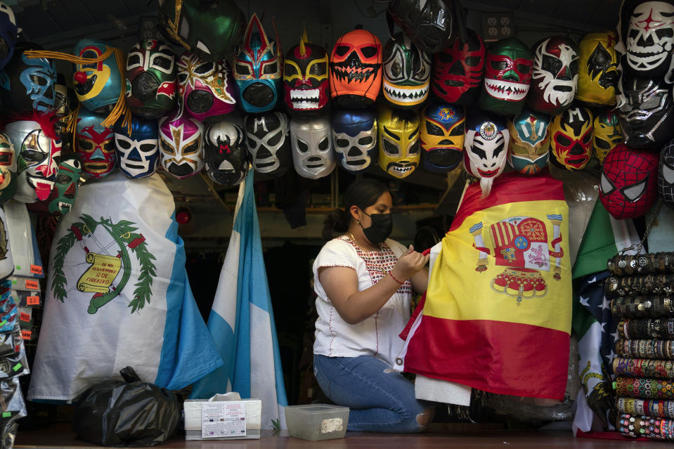 Clerk Wendy Ramirez uses a Spanish flag to wrap souvenirs while preparing to close the store for the day on Olvera Street in Los Angeles, Tuesday, June 8, 2021. Olvera Street has long been a thriving tourist destination and a symbol of the state's early ties to Mexico. The location of where settlers established a farming community in 1781 as El Pueblo de Los Angeles, its historic buildings were restored and rebuilt as a traditional Mexican marketplace in 1930s. As Latinos in California have experienced disproportionately worse outcomes from COVID-19, so too has Olvera Street. (AP Photo/Jae C. Hong)