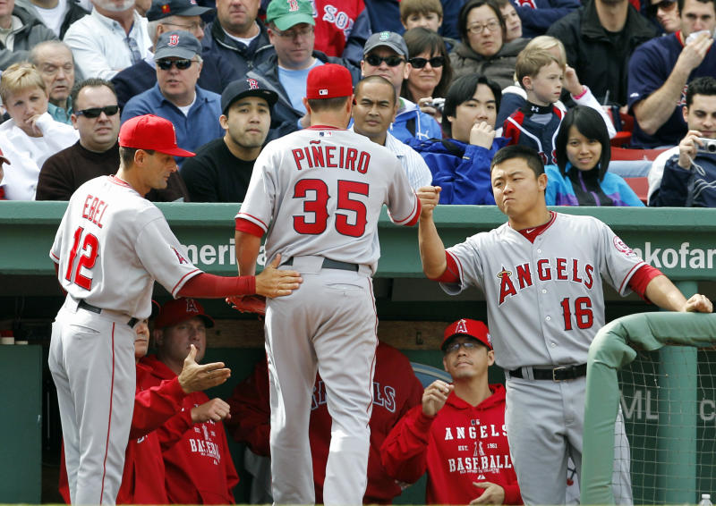 Los Angeles Angels starting pitcher Joel Pineiro (35) is greeted at the dugout by third base coach Dino Ebel (12) and catcher Hank Conger (16) as he leaves the baseball game in the sixth inning against the Boston Red Sox at Fenway Park in Boston Thursday, May 5, 2011. (AP Photo/Elise Amendola)