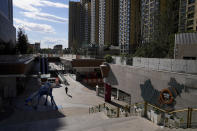 A man walks through a quiet Evergrande city plaza past a map showing Evergrande development projects and its apartment buildings in Beijing, Tuesday, Sept. 21, 2021. Global investors are watching nervously as the Evergrande Group, one of China's biggest real estate developers, struggles to avoid defaulting on tens of billions of dollars of debt, fueling fears of possible wider shock waves for the Chinese financial system. (AP Photo/Andy Wong)