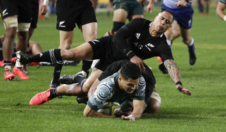 Australia's Noah Lolesio, bottom, scores his team's first try as New Zealand's Aaron Smith attempts a tackle during the Bledisloe rugby test between the All Blacks and the Wallabies at Stadium Australia, Sydney, Australia, Saturday, Oct. 31, 2020. (AP Photo/Rick Rycroft)