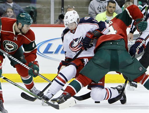 Columbus Blue Jackets right wing Cam Atkinson, center, gets tangled up with Minnesota Wild center Mikael Granlund, right, as he battles Granlund and Wild defenseman Clayton Stoner, left, for the puck during the second period of an NHL hockey game in St. Paul, Minn., Saturday, April 13, 2013. (AP Photo/Ann Heisenfelt)