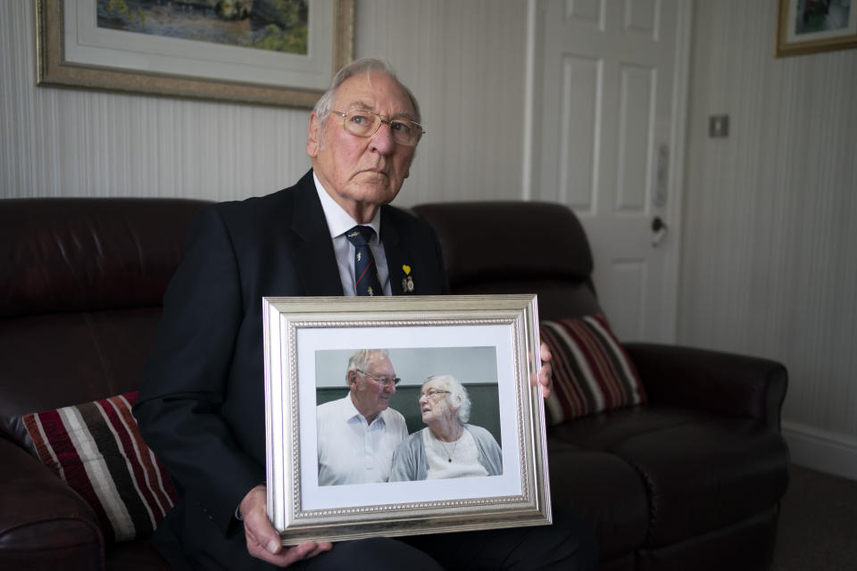 Gordon Bonner holds one of his favorite photographs of him with his late wife Muriel who, in April 2020 died of COVID-19, at his home in Leeds, England, Saturday Jan. 23, 2021. Bonner, 86, is just one of many hundreds of thousands of Britons toiling with grief because of the pandemic. (AP Photo/Jon Super)