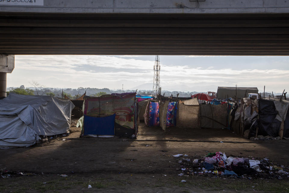 People who lost their homes in last year's hurricanes Eta and Iota live under tarps they set up under a bridge on the outskirts of San Pedro Sula, Honduras, Monday, Jan. 11, 2021. President Joe Biden has promised investment in Central America to get at the root causes of immigration, but no one expects to see any change soon. (AP Photo/Moises Castillo)
