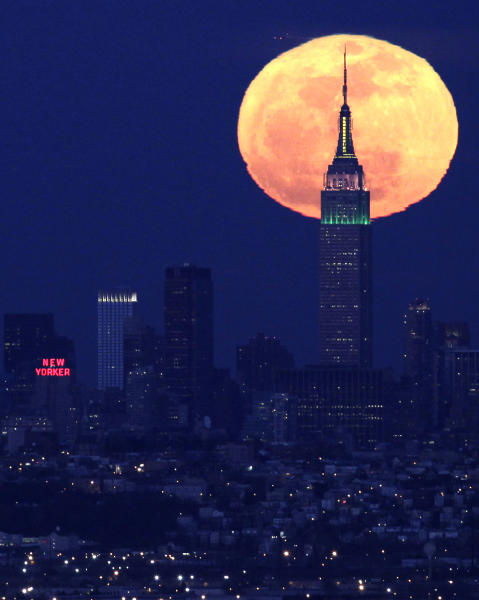 FILE - In this Friday, April 6, 2012, file photo, a full moon rises behind the Empire State Building in New York, as photographed in West Orange, N.J. The Empire State Building, Re/Max , the Burlington Coat factory, and the sandwich chain Potbelly are all going public next week. (AP Photo/Julio Cortez)