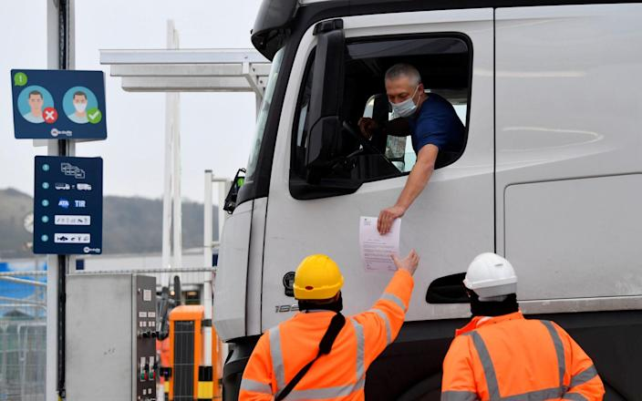 A lorry driver shows documentation to officials for both customs clearance and coronavirus test results as he arrives at the Eurotunnel on route to France - REUTERS