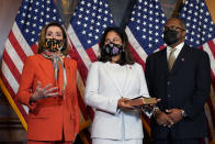 House Speaker Nancy Pelosi of Calif., left, speaks during a ceremonial swearing-in for Rep. Troy Carter, D-La., right, as his wife Ana Carter, center, watches on Capitol Hill in Washington, Tuesday, May 11, 2021. (AP Photo/Susan Walsh)