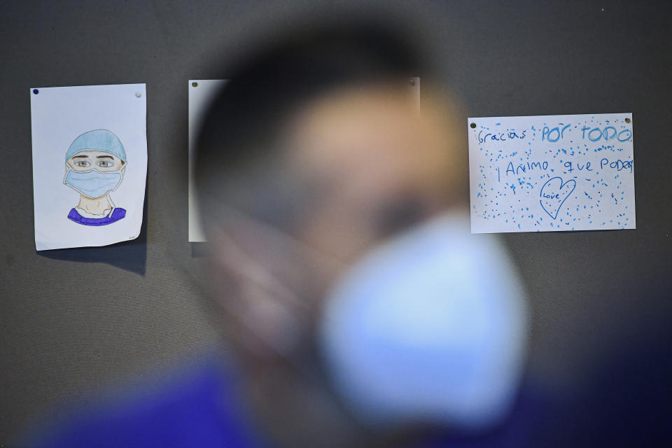 A man waits for the AstraZeneca COVID-19 vaccine in pictures supporting health workers, during a mass vaccination campaign at San Pedro Hospital, in Logrono, northern Spain, Wednesday, March 24, 2021. Spain resumed the use of the AstraZeneca vaccine on Wednesday. (AP Photo/Alvaro Barrientos)