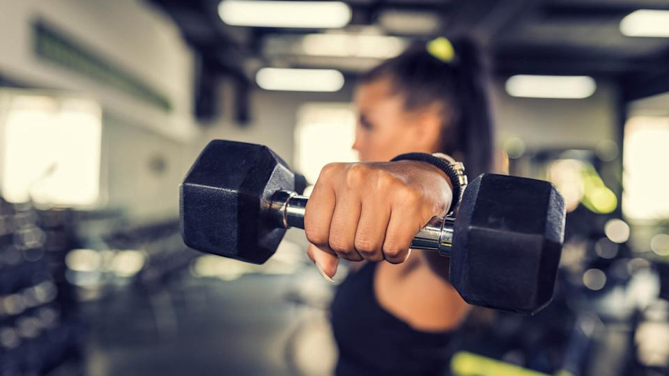 Young woman doing shoulder exercise using dumbbells.