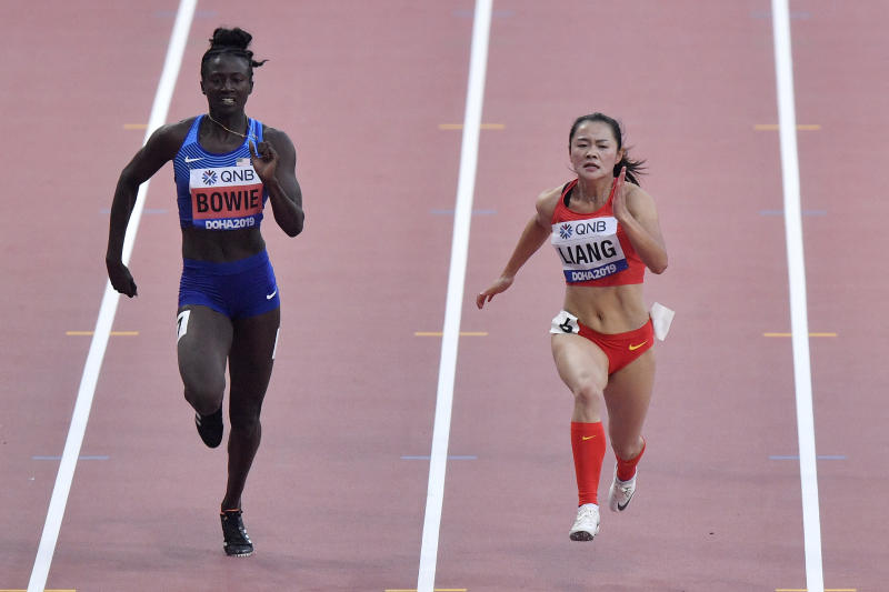 Tori Bowie, of the United States, and Xiaojing Liang, of China, right, compete in a women's 100 meter race heat during the World Athletics Championships in Doha, Qatar, Saturday, Sept. 28, 2019. (AP Photo/Martin Meissner)