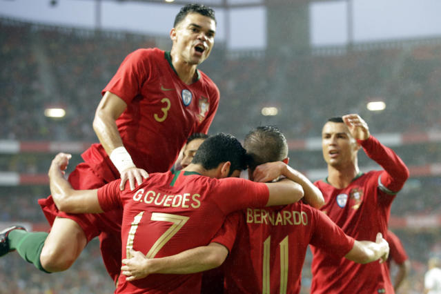 Portugal's Pepe, jumps from joy at his teammates, Portugal's Goncalo Guedes, 2nd from left, Bernardo Silva, 2nd from right, Cristiano Ronaldo, right, celebrating the opening goal during a friendly soccer match between Portugal and Algeria in Lisbon, Portugal, Thursday, June 7, 2018. (AP Photo/Armando Franca)