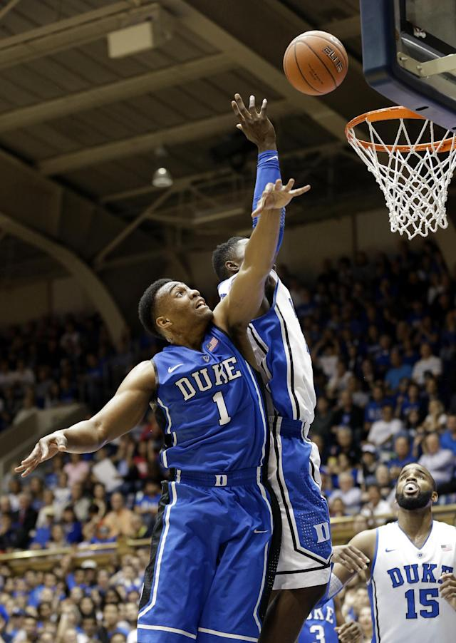 Duke Blue team's Jabari Parker (1) and White team's Semi Ojeleye reach for a rebound during the team's NCAA college basketball Blue-White preseason scrimmage during Countdown to Craziness event in Durham, N.C., Friday, Oct. 18, 2013. (AP Photo/Gerry Broome)