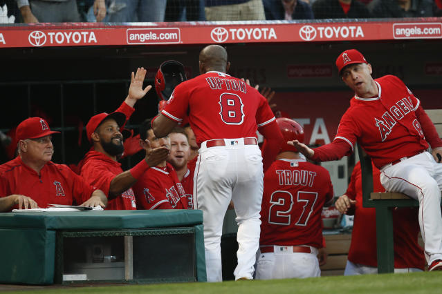 Los Angeles Angels' Justin Upton celebrates his two-run home run as he returns to the dugout during the first inning of the team's baseball game against the Houston Astros on Tuesday, May 15, 2018, in Anaheim, Calif. (AP Photo/Jae C. Hong)