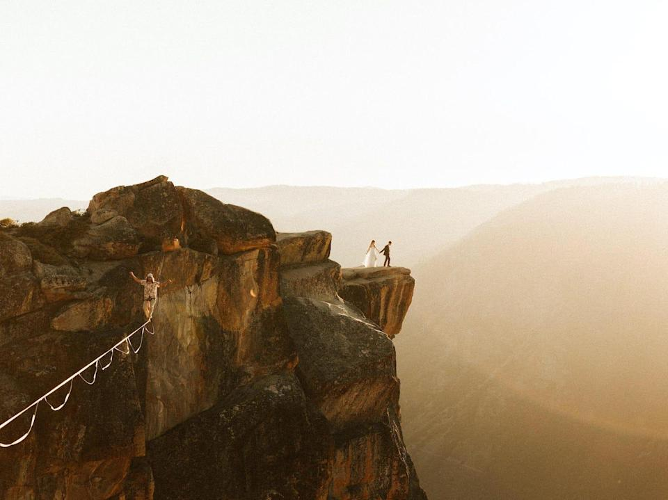 A slackliner is spotted in the forefront with a wedding couple in the background of Yosemite National Park.